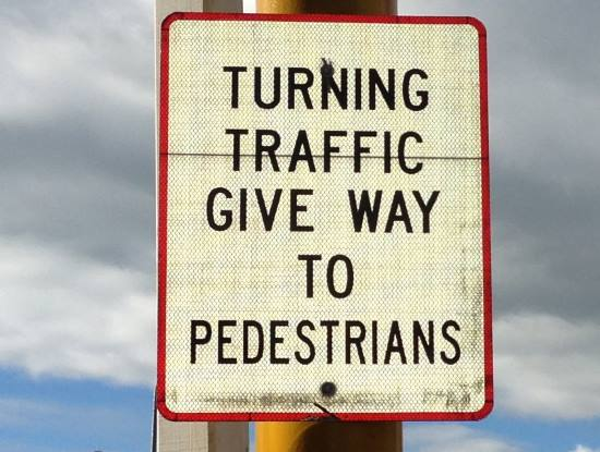 turning traffic must give way to pedestrians sign