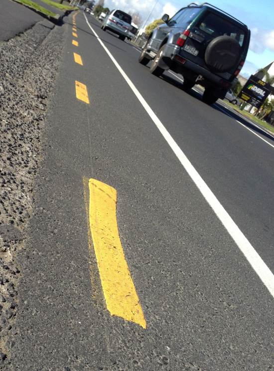 broken yellow line on the side of the road