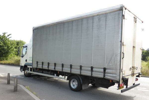 rigid truck with side guard between cab and rear wheels