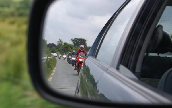 motorbike convoy reflected in car wing mirror